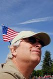 Man with flag. Man with sunglasses and american flag in baseball cap at May Day parade Stock Photo