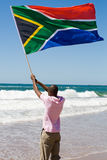 Man and flag. African man waving a south african flag on beach, new south africa 2010 world cup concept Royalty Free Stock Photos