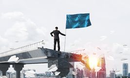 Man with flag presenting leadership concept. Rear view of confident businessman in suit holding flag in hand while standing among flying paper planes on broken Stock Photography