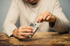 Man with flask at table Stock Photography
