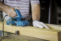 Man flattening a piece of wood with an electric planer Stock Photos