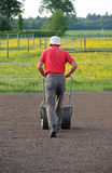 Man flattening the soil for preparing garden lawn Royalty Free Stock Photos