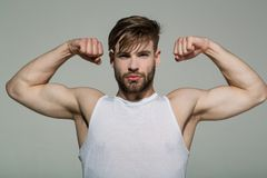 Man flex muscles, biceps, triceps on grey background stock photos