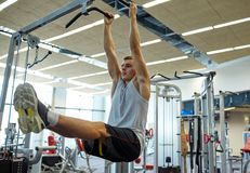 Man flexing abdominal muscles on pull-up bar. Sport, fitness, lifestyle and people concept - young man flexing abdominal muscles on pull-up bar in gym stock photos