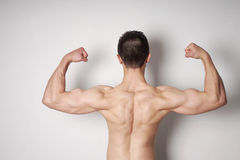 Man flexing biceps and back muscles Stock Photo