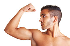 Man flexing his arm muscles. A young man flexing his biceps muscles Royalty Free Stock Image