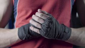Man flexing his fists before a fight. Close-up of a young Thai boxer hands hemp ropes are wrapped before the fight or stock image
