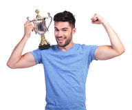 Man flexing his muscle and holding a trophy cup. Young man flexing his muscle and holding a trophy cup on shoulder stock photo