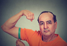 Man flexing his muscle measuring his biceps. Fitness goal achievement result Stock Photos
