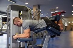 Man flexing leg muscles on gym machine Stock Photo