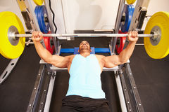 Man flexing muscles while bench pressing weights at a gym Royalty Free Stock Photography