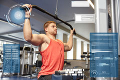 Man flexing muscles on cable machine gym Stock Images