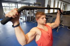 Man flexing muscles on cable machine gym Stock Photos