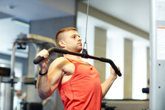 Man flexing muscles on cable machine gym Stock Photo
