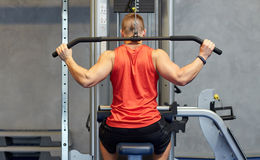 Man flexing muscles on cable machine gym Royalty Free Stock Photos