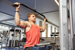 Man flexing muscles on cable machine gym Royalty Free Stock Image