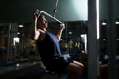 Man flexing muscles on cable machine in gym Stock Photo