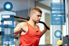 Man flexing muscles on cable machine gym Stock Photography