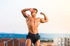Man flexing muscles on a rooftop. Masculine man flexing muscles on a rooftop Royalty Free Stock Images