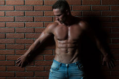 Man Flexing Muscles On Wall of Bricks. Handsome Young Man Standing Strong In The Gym And Flexing Muscles - Muscular Athletic Bodybuilder Fitness Model Posing Royalty Free Stock Photography