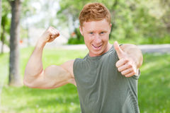 Man flexing and showing thumbs-up sign Royalty Free Stock Photography