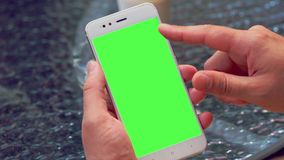 Man flicking through information on his mobile. With an upward flick of the finger in a close up view on the blank green screen stock footage
