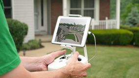 Man flies drone UAV in a residential neighborhood. A man flies a drone or UAV outside in a residential neighborhood. Screen image simulated stock video footage
