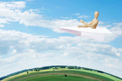 Man flies over the Earth in a toy paper plane Royalty Free Stock Image