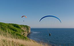 Two persons flies on paraplane above cliff break. A man flies on paraplane above cliff break, blue sky and sea on background Royalty Free Stock Photography