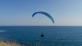 A man flies on paraplane above the sea. Blue sky on background Stock Photo