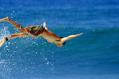 Man in Flight. A man seems to be in flight as he dives into the water Stock Photography