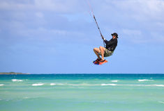 Man in a flight over water. Kitesurfing on the coast of Cuba Royalty Free Stock Images