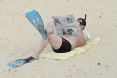 Man in flippers reads newspaper Royalty Free Stock Photography
