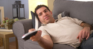 Man flipping through channels on couch Stock Images