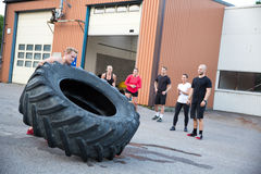 Man flipping heavy tires outdoor as workout Stock Images