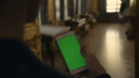 The man flips through a green screen on the phone with the hold at the museum stock footage
