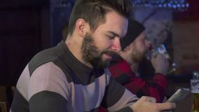 Man flips on his smartphone at the pub. Attractive young men flipping on his smartphone at the pub. Side view of bearded caucasian guy browsing social medias on Royalty Free Stock Image