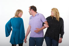 Man flirting with other woman. Man in a purple shirt is walking with his wife or girlfriend arm in arm. When he passes a blonde women in blue dress he turns his Stock Photo