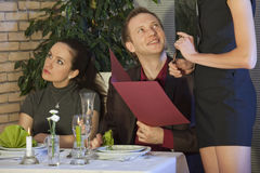 Man flirting with waitress. His girlfriend sitting unhappy Royalty Free Stock Photography