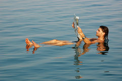 Man floating in a dead sea with newspaper royalty free stock photos