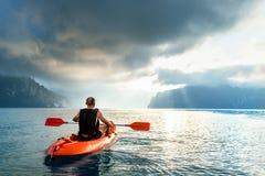 Man floating on kayak under sunrise sky on Cheow Lan Lake, Khao Sok national park, Thailand stock images