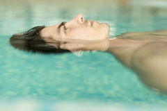 Man floating in the pool. Face of the man floating in the pool Stock Photos