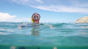 A man floating on the sea. A split shot of a man`s head and his body underwater stock video footage