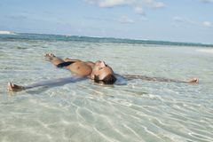 Man floating in water on the beach. With arms open Royalty Free Stock Photography