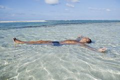 Man floating in water on the beach stock image