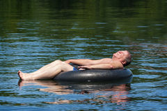 Man Floating in Water on Inner Tube Stock Images