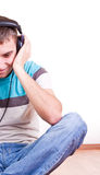 Man on the floor with earphones Stock Image