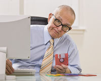 Man with Floppy Disc. An elderly businessman is seated in an office holding a floppy disk. He is looking at the camera. Horizontally framed shot stock photos