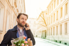 Man with flower bouquet talking on a mobile phone - city Stock Image