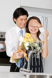 Man With Flowers. A good looking man surprising his wife with a bouquet of flowers at home royalty free stock photography